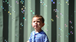 A young boy, surrounded by bubbles. 2013.